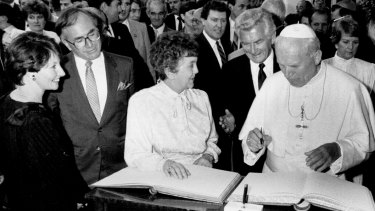 Pope John Paul II signs the visitors' book at Parliament House as Joan Child, Bob Hawke and John and Janette Howard look on. November 24, 1986