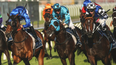Over the odds: Princess Posh (checked cap) beats Savatiano (royal blue) in the Newcastle Newmarket.