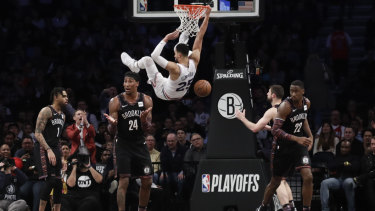 Brooklyn Nets' Rondae Hollis-Jefferson (24), Caris LeVert (22) and D'Angelo Russell (1) react to a dunk by Philadelphia 76ers' Ben Simmons (25) during the second half in Game 3 of a first-round NBA basketball playoff series in New York.