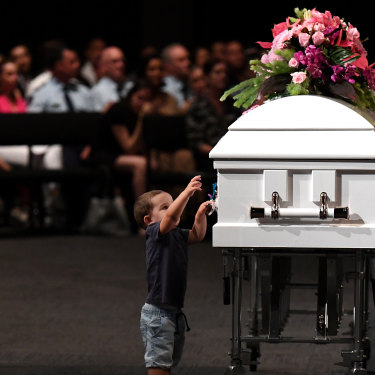 Hannah Clarke's nephew Tyler reaches to the coffin during the funeral for Hannah and her three children Aaliyah, Laianah and Trey.
