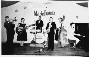 Marie Francis Family Band: young Marie is on the piano, her mother is on bass and her father is on drums.