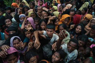 Rohingya refugees from Myanmar clamour for bamboo poles and tarpaulins to build shelters at a new camp near Kutupalong, Bangladesh, in 2017.