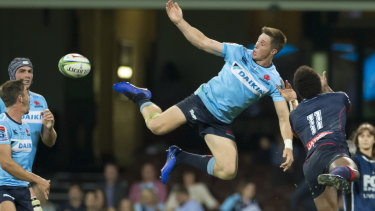 Folau-free zone: Alex Newsome of the Waratahs and Marika Koroibete compete for another bomb.