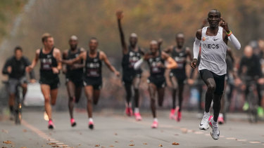 Eliud Kipchoge approaches the finish line after running 1:159 in a marathon in 2019, with his pacemakers celebrating behind.