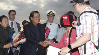Cambodian Prime Minister Hun Sen greets passengers disembarking from the MS Westerdam, owned by Holland America, at the port of Sihanoukville, Cambodia, last month.
