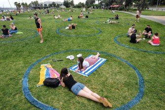 Beachgoers sat in 'social distancing circles' drawn by the council.
