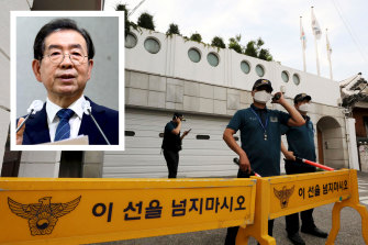 Police officers stand guard in front of the house of Seoul mayor Park Won-soon (inset) in Seoul.