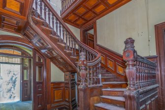 Red timber staircase inside the heritage-listed Lamb House at Kangaroo Point.