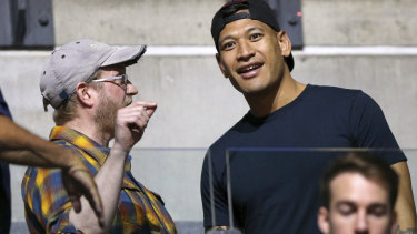 Support crew: Israel Folau was among the spectators as wife Maria took the court against Australia.