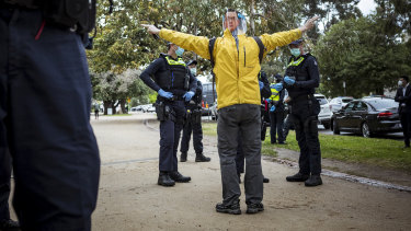 An anti-lockdown supporter is questioned by Victoria Police.