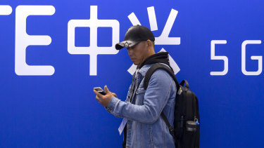 A man uses his smartphone near a display for 5G services from Chinese technology firm ZTE. China officially launched its 5G network on Friday.