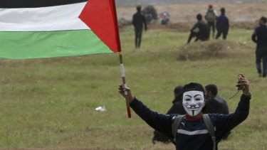 A masked protester waves his national flag near the fence of the Gaza Strip border with Israel, marking the first anniversary of Gaza border protests east of Gaza City on Saturday, March 30.