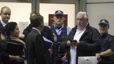Music promoter Andrew McManus, wearing a white T-shirt, was detained at Melbourne airport in 2015. He pleaded guilty to lying to police over a $702,000 bag of cash.
