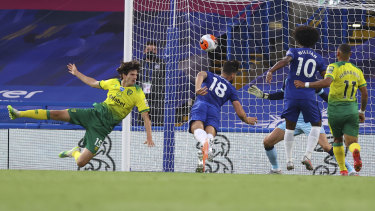 Chelsea's Olivier Giroud dives to head the ball into the net against Norwich.