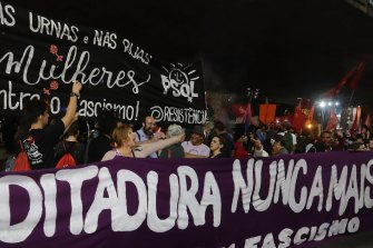 "Demonstrators carry a banner that reads in Portuguese ""Dictatorship never again,"" during a protest against Jair Bolsonaro in Sao Paulo, in 2018."