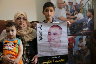 """Amal el-Halabi, 57, holds her grandson Fares, 18 months, while another grandson Amro, 7, holds a picture of his father Mohammed el-Halabi, at the family home in Gaza City.  The Arabic on the picture reads: """"The man of humanity""""."""