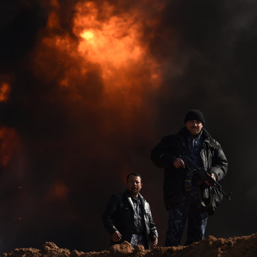 Two men provide security at Well 77 in the Qayyarah oil fields outside Mosul. Islamic State blew the wells up as they retreated.