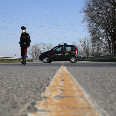 A sole Carabinieri officer at a checkpoint near Codogno, one of dozens of similar roadblocks set up in northern Italy.