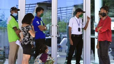 People wearing protective face masks queue to enter a shopping center in Dili, East Timor last week.