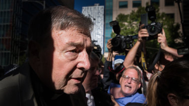 """George Pell outside Victoria's County Court, where hecklers yelled that the cardinal was going to """"burn"""" and """"rot"""" in hell."""