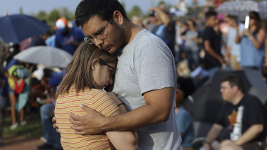 Mamy Garcia comforts his girlfriend Jackie Saucedo at the Hope Border Institute prayer vigil on Sunday in El Paso, Texas, a day after the mass shooting.