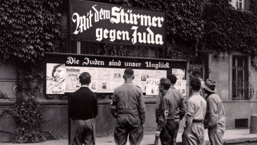 """The anti-Semitic Nazi newspaper Der Sturmer is put up in the street of Worms, Germany, under the headline """"The Jews are our Misfortune""""."""