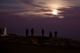 People maintain a social distance due to the coronavirus pandemic while waiting for a full moon to emerge from behind the clouds in Maroubra.
