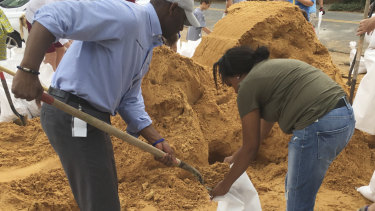 Tallahassee mayor and Democratic gubernatorial candidate Andrew Gillum, left, helps Eboni Sipling fill up sandbags in Tallahassee, Florida, on Monday.