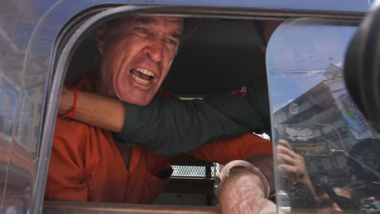 Australian filmmaker James Ricketson speaks from a prison truck during a lunch break at Phnom Penh Municipal Court on Friday.