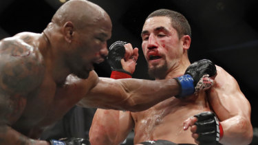 Coaching: UFC middleweight champion Robert Whittaker dodges a punch from Yoel Romero.