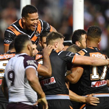 Wests Tigers players celebrate after Robbie Farah's match-sealing try in the opening round of the 2019 season, which Lawrence watched from home.