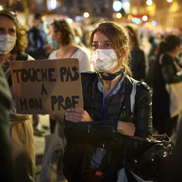 "A woman holds a sign reading ""Do not touch my teacher"" during a national tribute to Samuel Paty in Paris."