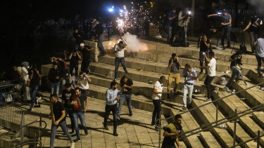 Palestinians escape from a stun grenade fired by Israeli police officers during clashes at Damascus Gate during Ramadan in Israeli-occupied East Jerusalem.