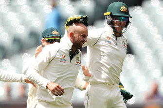 Nathan Lyon, left, celebrates with Tim Paine  after taking the wicket of Shan Masood.