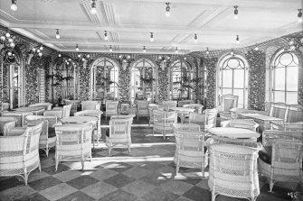 A photo by shipmaker Harland & Wolff's official photographer Robert John Welch of the cafe on-board the RMS Olympic, taken while the ship was in the fitting yard. Johannes Vogelin made coffee on the Olympic and its sister ship the Titanic.