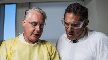 Professor Michael Buckland from the Concussion Legacy Foundation and former NFL player Colin Scotts examine a brain.