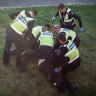 An image from CCTV showing police pinning pensioner John to the ground.