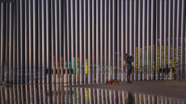 A woman takes a snapshot by the border fence between San Diego, California, and Tijuana, as seen from Mexico.