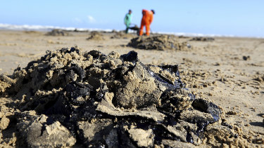 Workers remove oil from Viral Beach, in Aracaju, Brazil.