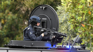 An armed officer is seen at the Westbury Street standoff.