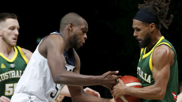 The USA's Kris Middleton is stripped of the ball by Australia's Patty Mills during game one at Marvel Stadium on Friday night.