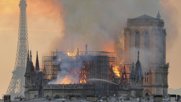 Flames and smoke rise from the blaze after the spire toppled over on Notre-Dame.
