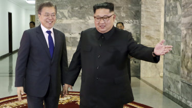 South Korea's Moon Jae-in, left, is guided by North Korean leader Kim Jong-un, right, at the northern side of Panmunjom in North Korea during their surprise meeting on Saturday.