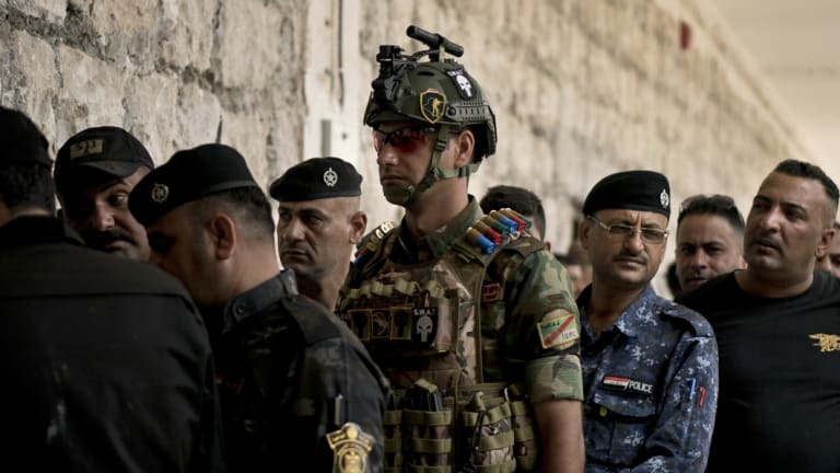 Soldiers wait to cast their ballots in early voting for Iraq's security forces, prisoners and hospital patients ahead of Saturday's national parliamentary elections.