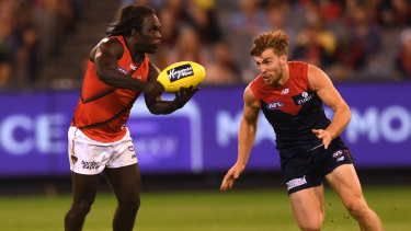Pressure point: Demon Jack Viney lines up Essendon's Anthony McDonald-Tipungwuti.