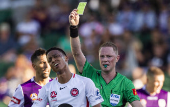 Keanu Baccus of the Wanderers gets a yellow card against Perth Glory on Sunday.