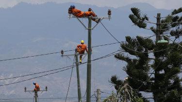 Workers take a break as they restore electricity in earthquake-hit Balaroa, Palu.