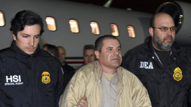 "US authorities escort Mexican drug lord Joaquin ""El Chapo"" Guzman from a plane in New York last year."