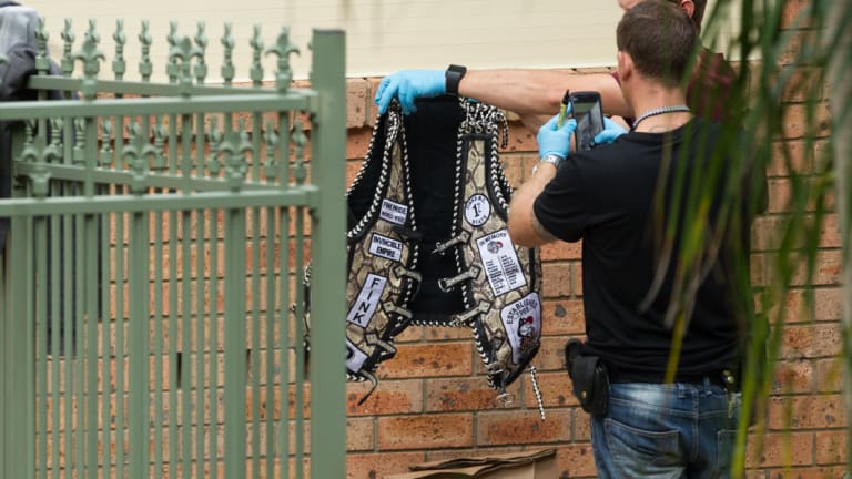 Police hold up an item of Finks clothing during raids in the Hunter last week.