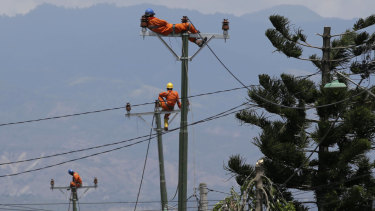 Workers take a break as they restore electricity in earthquake-hit Balaroa, Palu.